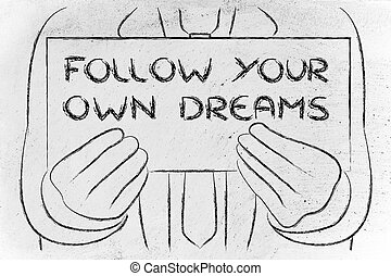 business man holding sign saying Follow your dreams
