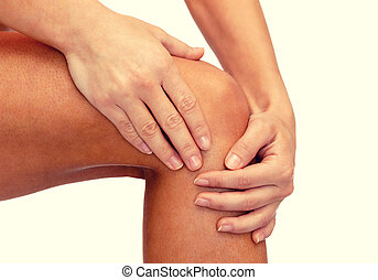 close up of female hands holding knee - fitness, healthcare...