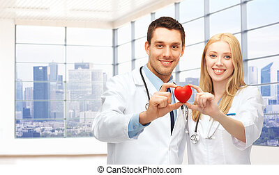 happy young doctors cardiologists with red heart - medicine,...