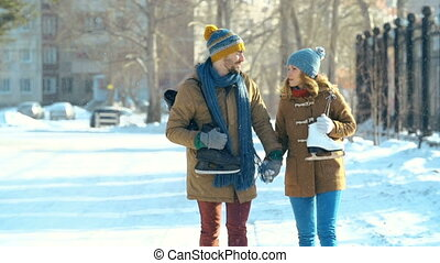 Hand-in-Hand - Static shot of young couple with skates...