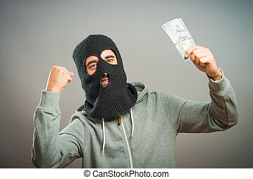 man close up thief in a mask  holding the money