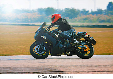 young man riding motorcycle in asphalt road curve with with...
