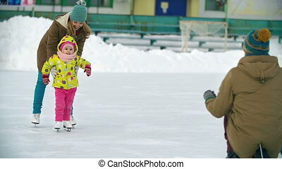 At the Skating Rink - Joyous family at the skating rink,...
