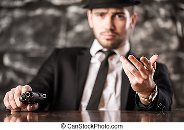 Gangster. - Confident, gangster man in suit and hat is...