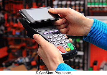 Paying with NFC technology on mobile phone - Hand of woman...