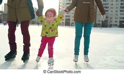 Fine Winter Day - Tracking shot of family of three holding...
