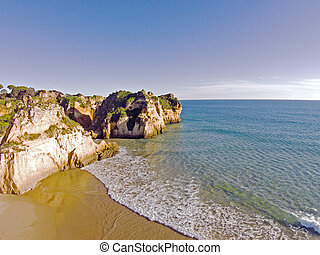 Aerial from rocks and ocean at Praia tres Irmaos in Algarve...