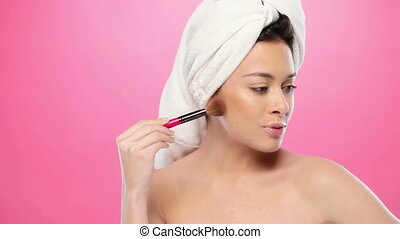 gorgeous brunette in bathrobe on pink applying her makeup