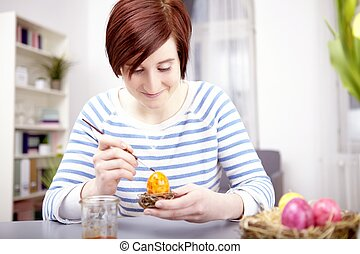 young girl paint eggs for easter - young happy girl with...