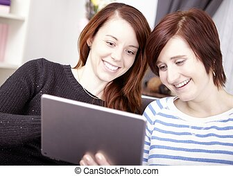 two young girls with tablet computer - portrait of two happy...