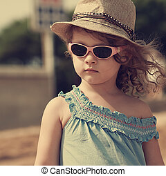 Kid in sun glasses and fashion hat outdoors. Vintage closeup...