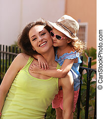 Happy young mother with her cute kid girl in sun glasses...