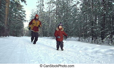 Run Fun - Shaky camera shot of father running after son in...