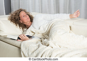 woman on couch reading a book
