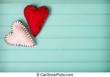 Two felt hearts on a retro turquoise background