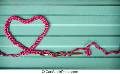 A crochet chain in the shape of a heart on a retro turquoise...
