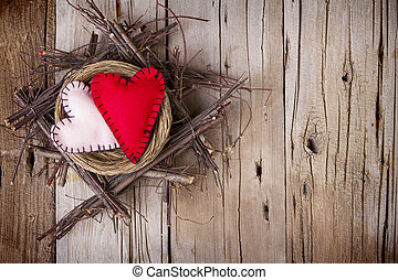 Two felt hearts in a wooden nest - Two felt hearts in a...