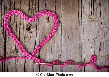 A crochet chain in the shape of a heart on a rustic wooden...