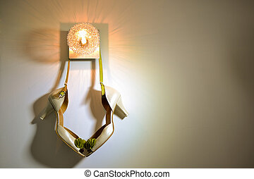 Bridal shoes hanging from a wall lamp