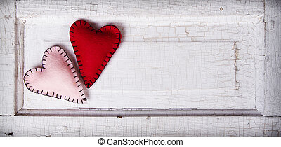 Two felt hearts on an antique wooden background