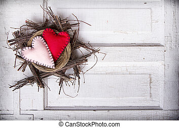 Two felt hearts in a nest on a antique wooden background