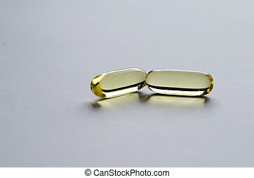 Two yellow transparent capsules on light background