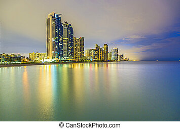 skyline of sunny isles beach by night with reflection in the...
