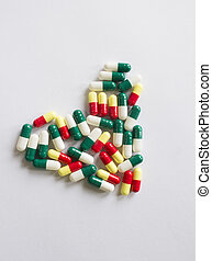 Heart-shaped bi-colored capsules on white background