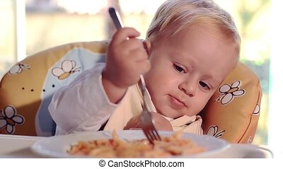 funny baby eating pasta - baby boy on high chair eating...