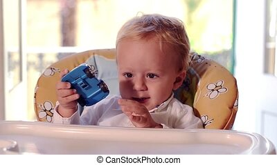 a baby boy and his toy car - kid on high chair playing with...