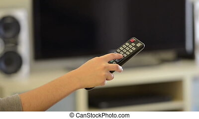 Changing Channels on TV - Person holding a remote control...