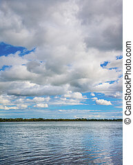 Summer Cloud Scape - Clouds in summer heavenly sky over lake