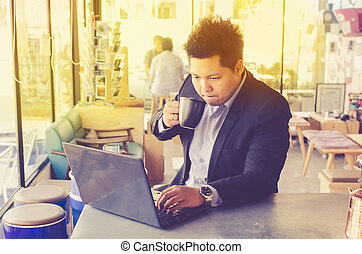 Young business man with a cup and a laptop in a cafe, photo...