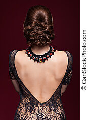 Young beautiful woman in black dress from back side on...
