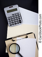 Calculator with office documents and magnifying glass.