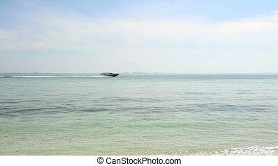 speedy motor boat sail in azure sea against rocky island