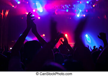 Cheering crowd having fun at a concert.