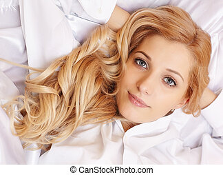 Young blonde woman in the bed - Young happy blonde woman in...