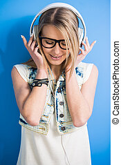 Trendy woman - Trendy, blonde girl is listening a music with...
