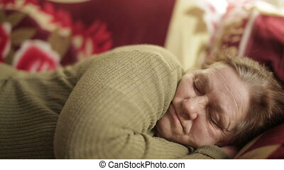 Grandmother sleeps during the day on sofa