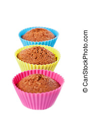 Muffins - Fresh muffins in colorful forms on white...