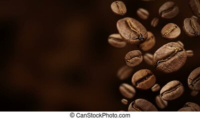 Roasted coffee beans falling down in front of dark background.