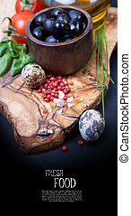 Black olives with bottle of oil on a wooden table