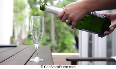 Pouring Champagne - Woman pours bubbly champagne into a...