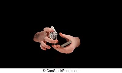 Unusual trick with cards on black background, slow motion -...