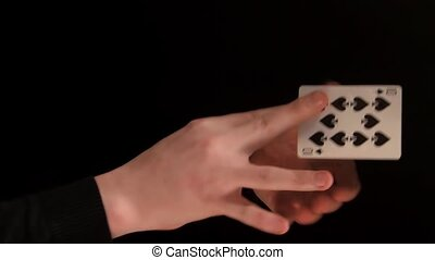 Hands of magician doing a magic trick with cards on black...