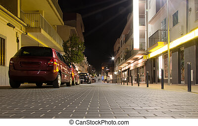 Street with parked cars at night.
