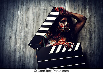 creepy cinema - Filming a horror movie Female zombie holding...