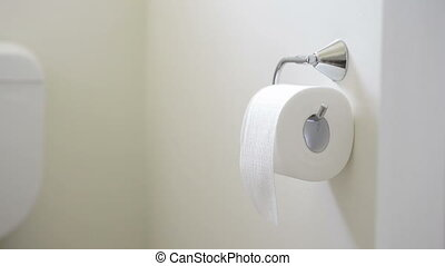 Toilet Paper - Person tears off toilet paper tissue in the...