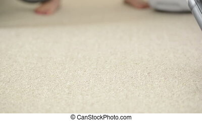 Vacuum Cleaner - Woman using vacuum cleaner to vacuum carpet...